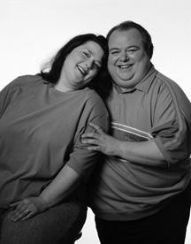 photo of middle-aged large man and large woman smiling