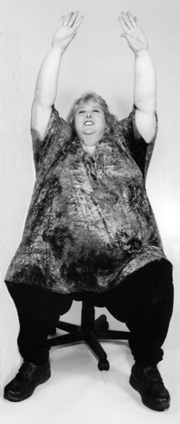 photo of large woman stretching her arms up while seated