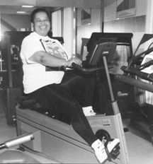 photo of large woman peddling a stationary bicycle