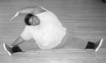 photo of large woman doing leg stretches on the floor
